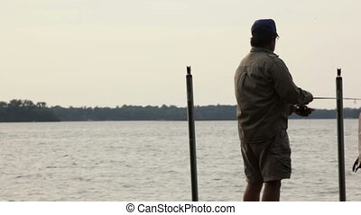 Mid-aged man fishing - Mid-aged man, fishing off a dock on a...