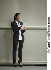 Young Indian businesswoman standing outside using Tablet PC...