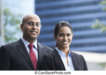 Indian business man and woman in a modern urban setting. -...