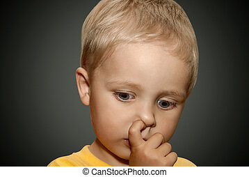 Young boy picking his nose.