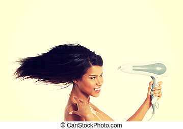 Woman with long hair holding blow dryer - Woman with long...