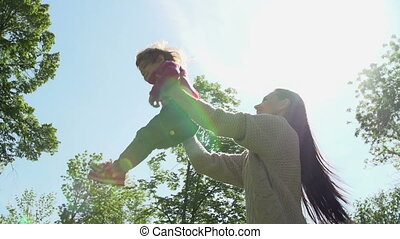 Up in the Air - Slow motion of happy mother jigging daughter...