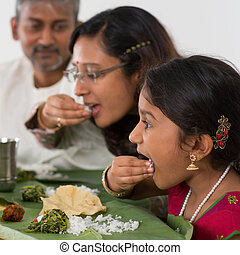 Indian family dining at home. Candid photo of Asian people...