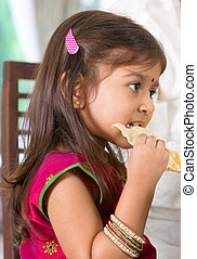 Indian girl eating snack. - Indian family dining at home....