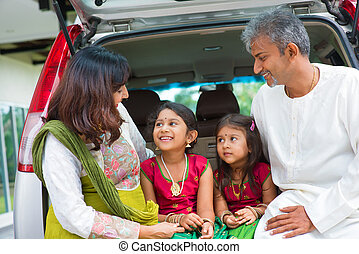 Indian family in car infront new house.