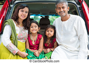 Indian family sitting in car.