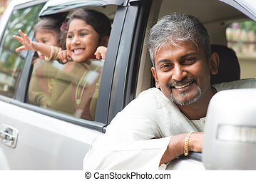 Indian father driving new car.
