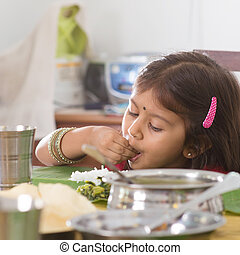 Indian girl eating rice - Indian family dining at home...