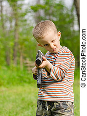 Cute boy aiming with machine gun - Cute boy wearing striped...