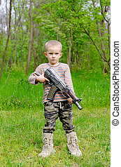 Young boy posing with machine gun - Young boy wearing...