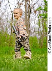 Young boy posing with machine gun - Young boy wearing...