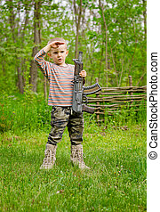 Boy carrying a machine gun saluting - Young boy carrying a...
