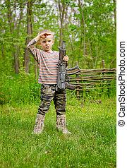 Boy carrying a machine gun saluting - Young boy carrying a...