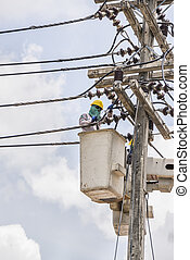 Electrical utility worker in a bucket fixes a problem with a pow