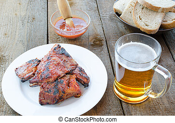 Spareribs on grill with hot marinade, czech beer and bread