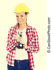 Woman holding drill and wearing safety helmet - Young casual...