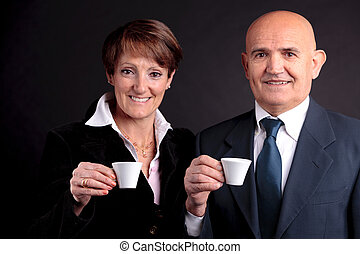an elderly couple holding up two cups of espreso coffee - a...