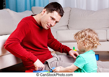 Smiling father playing with his son