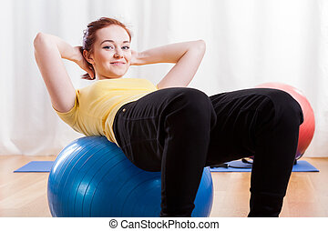 Girl doing crunches on gym ball - Happy girl doing crunches...