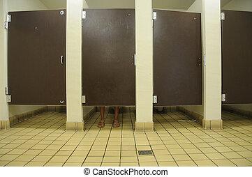 Bathroom Feet - Feet showing under bathroom stall door, in...