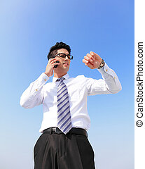 Time - business man look watch with blue sky