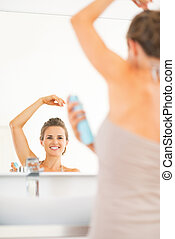 Happy young woman applying deodorant on underarm in bathroom