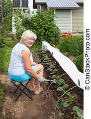 Mature woman working in her garden in June