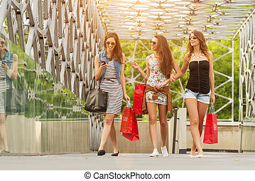 Three beautiful woman on the bridge, hand held shopping bags