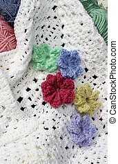 White afghan and colorful flowers - Crocheted flowers on a...