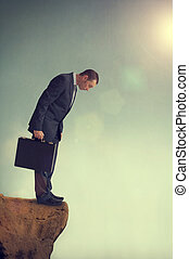 business dilemma - businessman facing a dilemma on a cliff...