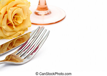 Dinner place setting. Knife and fork and glass with yellow rose on white