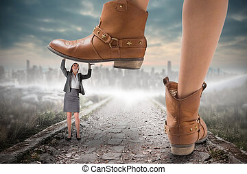 Composite image of cowboy boots stepping on businesswoman...