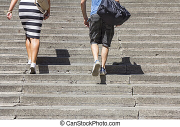 Climbing on concrete stairs - A woman and man climbing on...