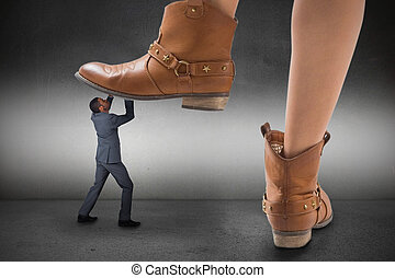 Composite image of cowboy boots stepping on businessman on...