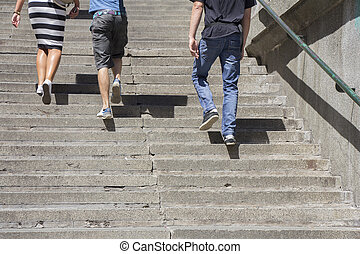 Climbing on stairs - A woman and two man climbing on...