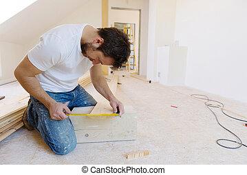 Wooden flooring - Handyman installing wooden floor in new...
