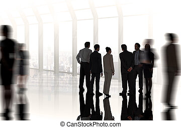 Composite image of business colleagues standing against room...