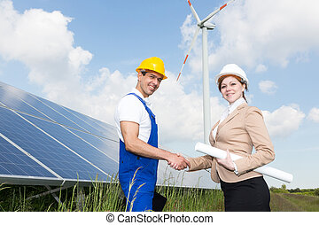 Engineers shake hands in front of solar panels and wind turbine