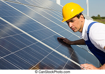 Engineer or installer inspecting solar energy panels - An...