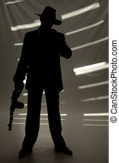 Businessman with a gun - businessman in hat with a gun in...