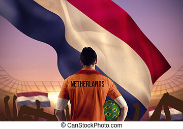 Composite image of netherlands football player holding ball...