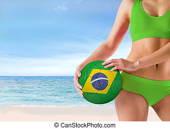 Composite image of fit girl in green bikini holding brasil...