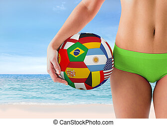 Composite image of fit girl in green bikini holding flag...