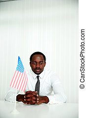 Serious african businessman sitting at the table with USA flag