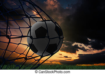 Composite image of football in back of the net under dark...