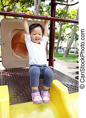 Happy child play on slide playground area in the park, asian