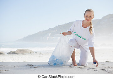 Blonde activist picking up trash on the beach on a sunny day
