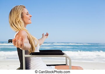 Wheelchair bound blonde smiling on the beach on a sunny day
