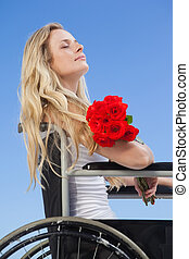 Wheelchair bound blonde smiling on the beach holding roses...