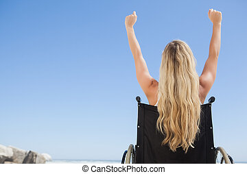 Wheelchair bound blonde sitting on the beach with arms up on...